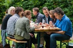 Gasten eten gezellig samen aan tafel tijden een barbecue